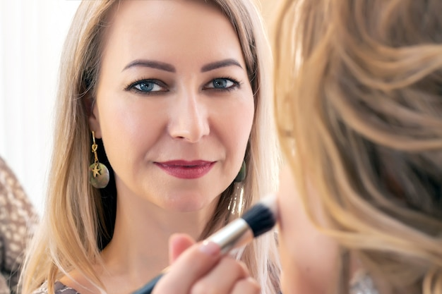 Professionele make-up artiest werken met client in salon.