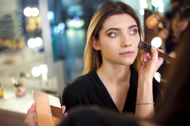 Professionele make-up artiest werken met mooie jonge vrouw. modieuze vrouw