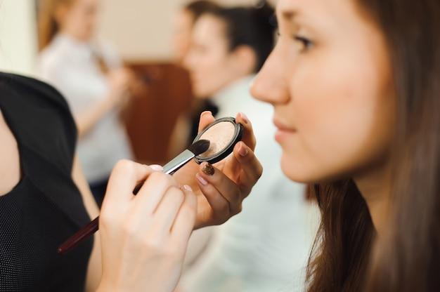 Professionele make-up artiest werken met mooie jonge vrouw.