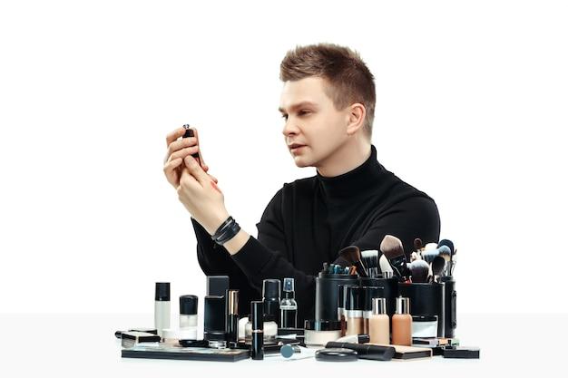 Professionele make-up artist met tools geïsoleerd op witte studio achtergrond. de man in het vrouwelijk beroep. gendergelijkheid concept