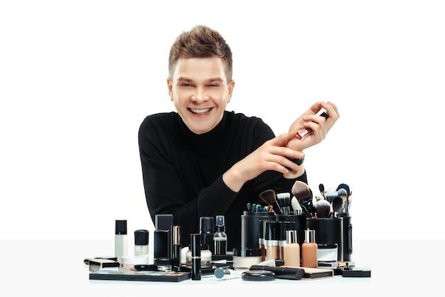 Professionele make-up artist met tools op wit wordt geïsoleerd. de man in vrouwelijk beroep. gendergelijkheid concept