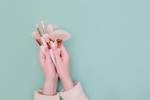 Professionele make-up borstel cosmetische in vrouwelijke hand schoonheidsspecialiste op neo mint achtergrond. bovenste horizontale weergave copyspace