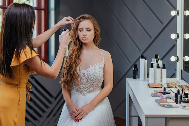 Professionele make-up en kapselkunstenaar die make-up voor de bruid maakt. professionele cosmetica