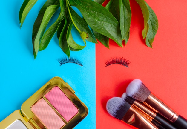 Professionele make-up tools oogschaduw en borstels op een gekleurde blauwe en rode achtergrond in de vorm van een gezicht met valse wimpers