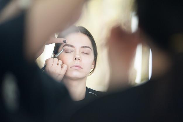 Professionele make-up voor een vrouw in een schoonheidsstudio