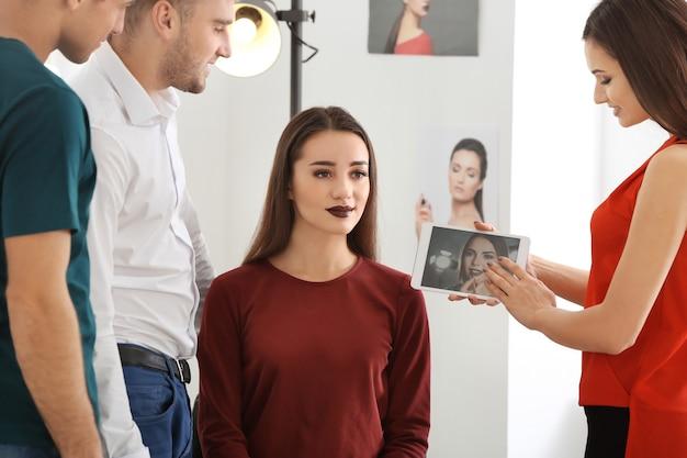 Professionele make-upartiest die stagiaires in salon onderwijst. leerlingwezen concept