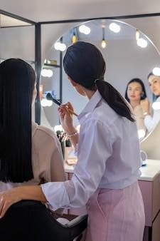 Professionele make-upartiest die vrouwelijke cliënt lesgeeft die blush op gezichtsborstel aanbrengt tijdens masterclass