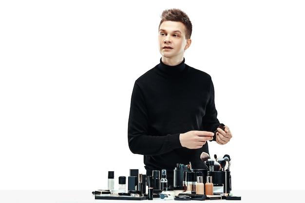 Professionele make-upartiest met hulpmiddelen die op witte ruimte worden geïsoleerd