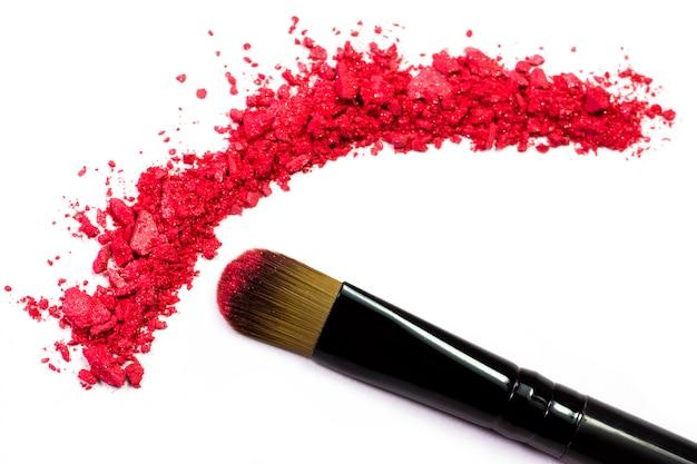 Professionele make-upborstel op rode geplette oogschaduw