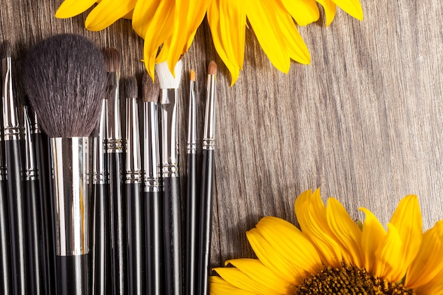 Professionele make-upborstels naast mooie wilde bloemen op houten achtergrond