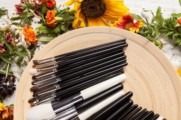 Professionele make-upborstels op plaat naast wilde bloemen op houten achtergrond