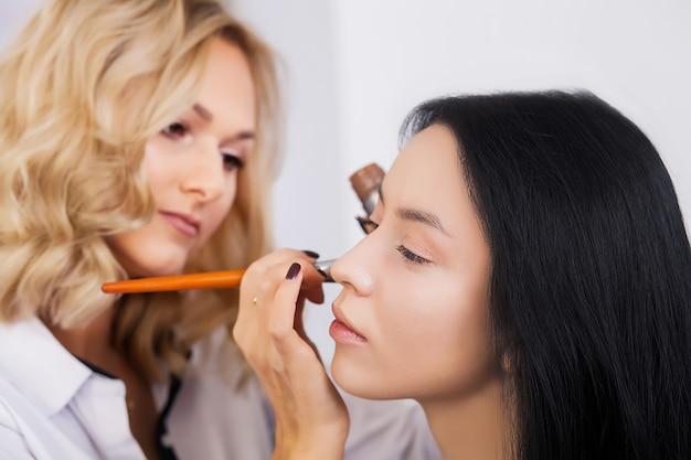 Professionele make-upkunstenaar die met mooie jonge vrouw werkt