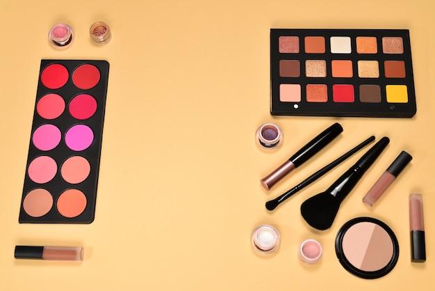 Professionele make-upproducten met cosmetische schoonheidsproducten, oogschaduw, pigmenten, lippenstiften, penselen en hulpmiddelen op beige achtergrond. ruimte voor tekst of ontwerp.