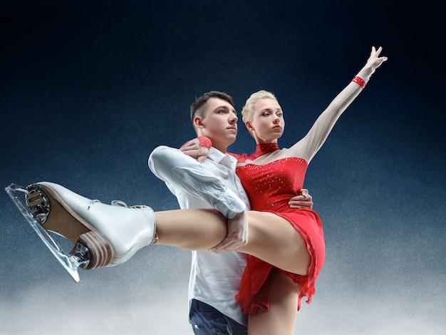 Professionele man en vrouw kunstschaatsers die show of competitie op ijsarena uitvoeren