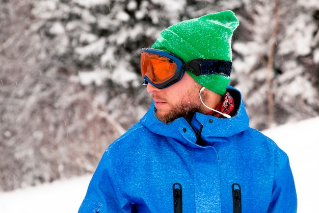 Professionele man snowboarder in helder blauwe sportkleding in besneeuwde hooggebergte. concept rest apres ski