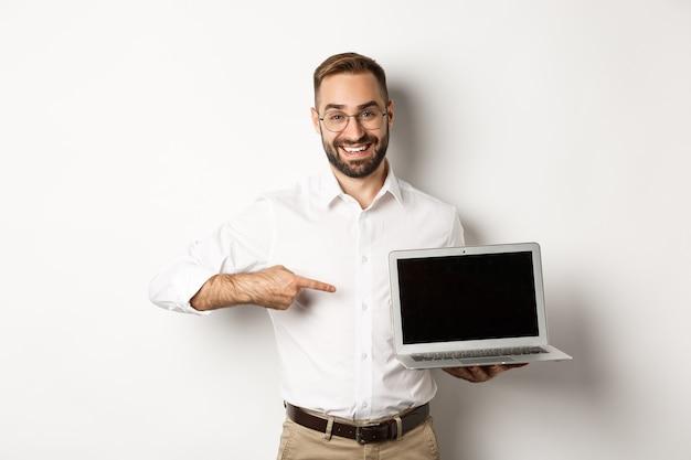 Professionele manager die webpagina op het scherm van de laptop toont, wijzend op de computer, staande op een witte achtergrond.