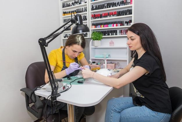 Professionele manicure in een schoonheidssalon. de meester brengt een kleurloze vernis aan op de nagels van de klant.