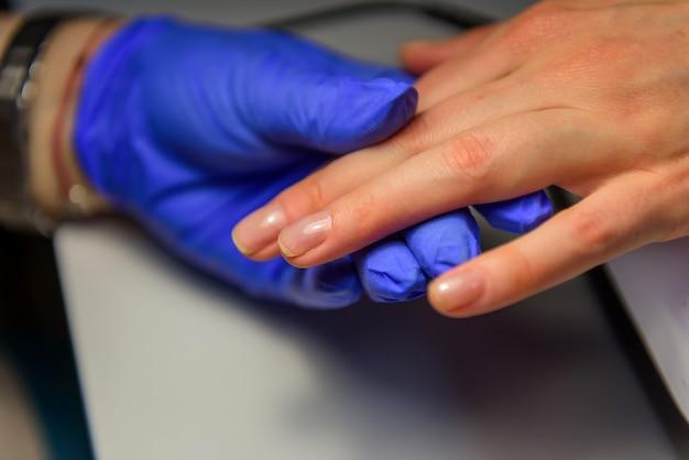 Professionele manicure in salon, het aanbrengen van de basis onder de lak. handen van meester in handschoenen en vingers van de klant, glans op nagels, close-up