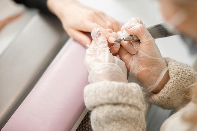 Professionele manicure meester doet nagels voor cliënt in de schoonheidssalon