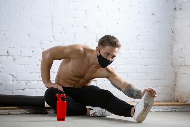 Professionele mannelijke atleet training op bakstenen muur achtergrond met gezichtsmasker.