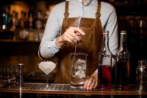 Professionele mannelijke barman roeren een alcoholische drank met ijs in de maatbeker