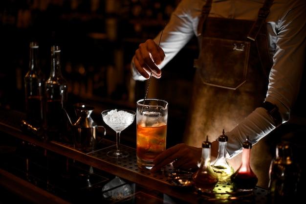 Professionele mannelijke barman roeren een cocktail in de maatbeker