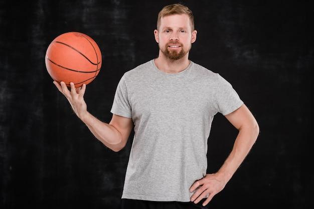 Professionele mannelijke basketbaltrainer of speler met bal die zich voor camera tegen zwarte achtergrond bevinden