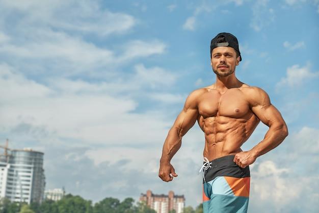 Professionele mannelijke bodybuilder die zijn spieren toont.