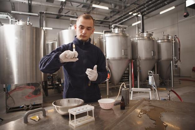 Professionele mannelijke brouwer die kwaliteitstests uitvoert in de bierfabriek, kopie ruimte