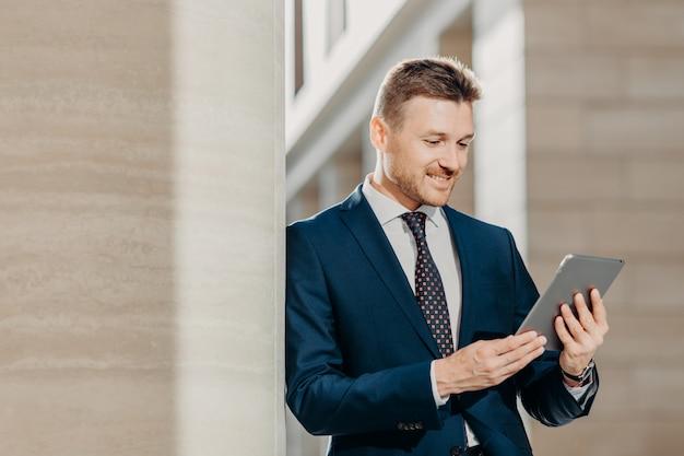 Professionele mannelijke ceo in elegant pak, controleert bankrekening op tablet in internet