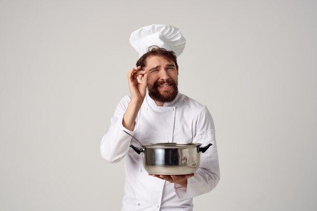 Professionele mannelijke chef-kok in een restaurant met een pan in de handen van het verlenen van service