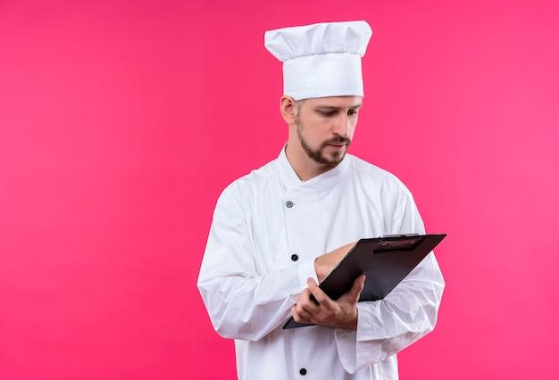 Professionele mannelijke chef-kok in wit uniform en het klembord van de kokhoedholding bekijkt het met ernstig gezicht dat zich over roze achtergrond bevindt