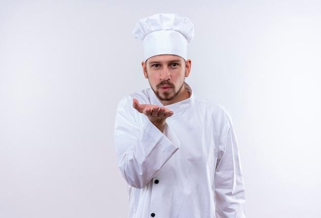 Professionele mannelijke chef-kok in wit uniform en kok hoed blaast een kus met de hand op lucht wordt mooi staande op witte achtergrond
