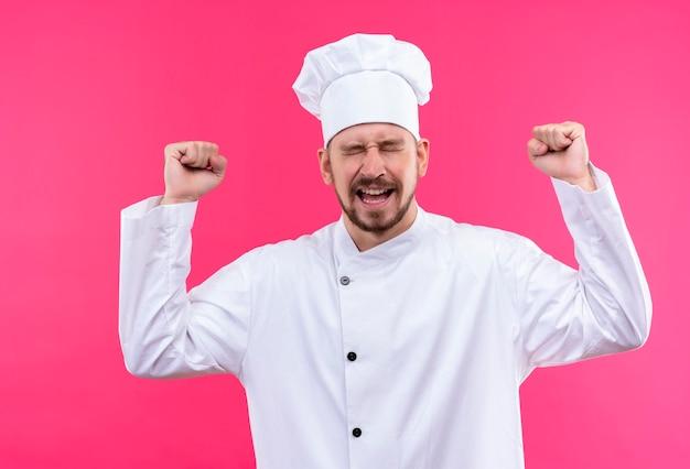 Professionele mannelijke chef-kok in wit uniform en kok hoed ceazy blij gebalde vuisten glimlachend met gesloten ogen verheugend zijn succes staande over roze achtergrond