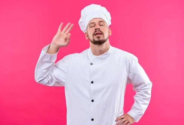 Professionele mannelijke chef-kok in wit uniform en kok hoed doet ok teken met gesloten ogen permanent over roze achtergrond
