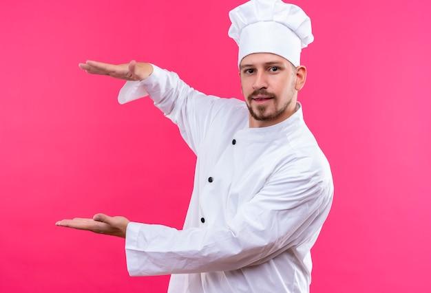 Professionele mannelijke chef-kok in wit uniform en kok hoed gebaren met handen weergegeven: grootte, symbool meten op roze achtergrond