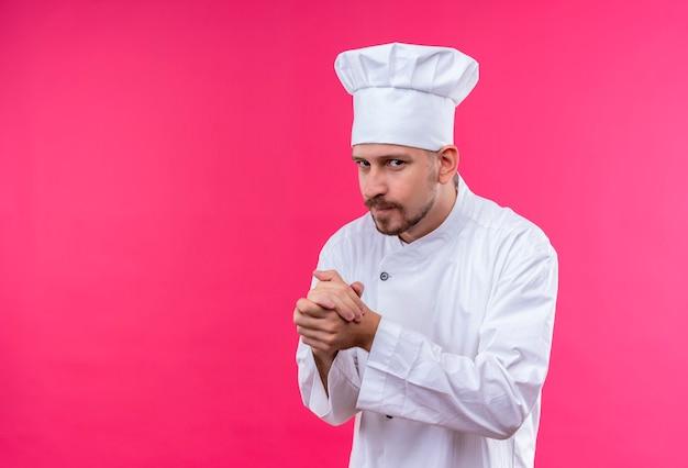 Professionele mannelijke chef-kok in wit uniform en kok hoed handen wrijven kijken camera sluw staande over roze achtergrond