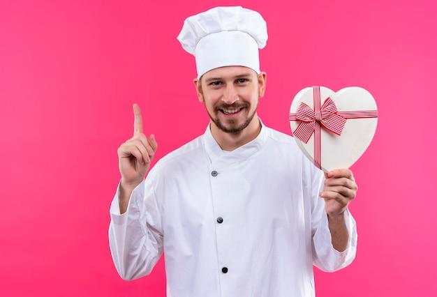 Professionele mannelijke chef-kok in wit uniform en kok hoed houden geschenkdoos wijzende vinger glimlachend vrolijk over roze achtergrond