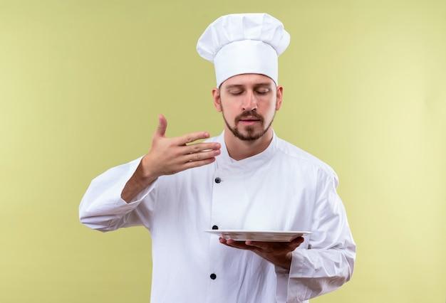 Professionele mannelijke chef-kok in wit uniform en kok hoed met plaat inhaleert aangename geur van voedsel staande over groene achtergrond