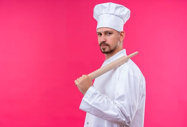 Professionele mannelijke chef-kok in wit uniform en kok hoed met rollende roze kijken zelfverzekerd staande over roze achtergrond