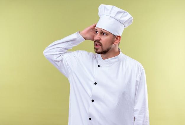 Professionele mannelijke chef-kok in wit uniform en kok hoed op zoek verward zijn hoofd krabben voor fout staande over groene achtergrond