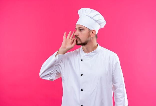 Professionele mannelijke chef-kok in wit uniform en kok hoed opzij kijken stilte gebaar maken als zijn mond sluiten met een rits permanent over roze achtergrond