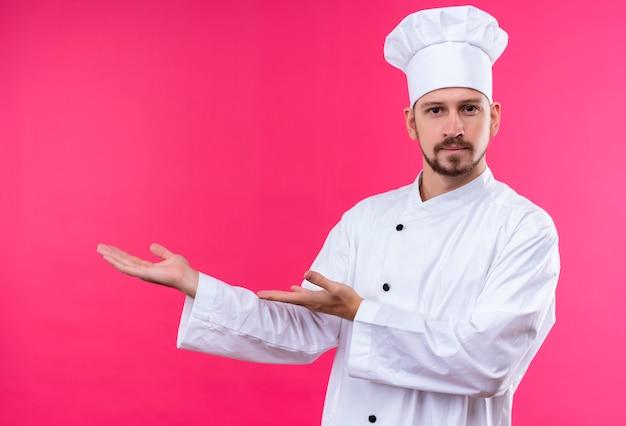 Professionele mannelijke chef-kok in wit uniform en kok hoed presenteren kopie ruimte met armen van zijn handen permanent over roze achtergrond