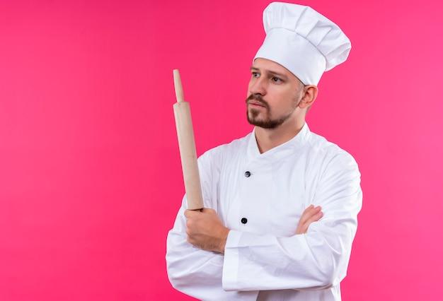 Professionele mannelijke chef-kok in wit uniform en kok hoed staande met gekruiste armen houden deegroller met peinzende uitdrukking op gezicht over roze achtergrond