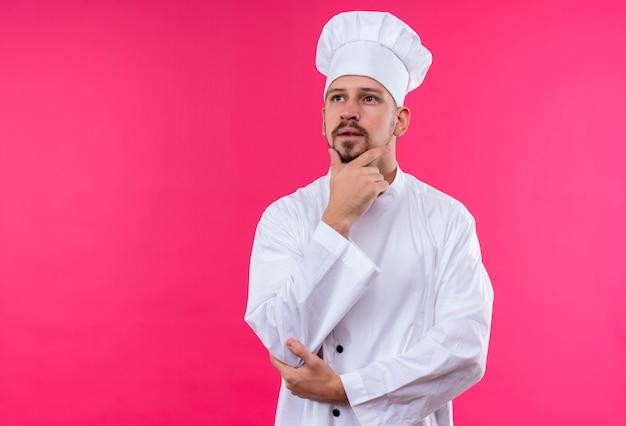 Professionele mannelijke chef-kok in wit uniform en kok hoed staande met hand op kin denken met dromerige blik over roze achtergrond