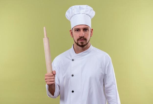 Professionele mannelijke chef-kok in wit uniform en koken hoed met deegroller kijken zelfverzekerd staande over groene achtergrond