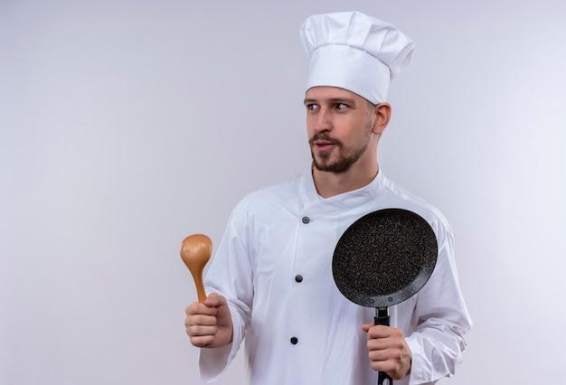 Professionele mannelijke chef-kok in wit uniform en koken hoed met koekenpan en houten lepel opzij kijken gelukkig en positief staande op witte achtergrond