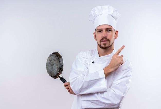 Professionele mannelijke chef-kok in wit uniform en koken hoed met koekenpan wijzend met vinger naar de kant op zoek zelfverzekerd staande op witte achtergrond