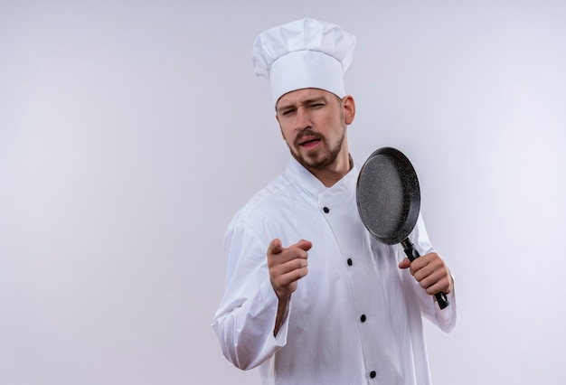 Professionele mannelijke chef-kok in wit uniform en koken hoed met koekenpan wijzend naar camera met zelfverzekerde blik staande op witte achtergrond