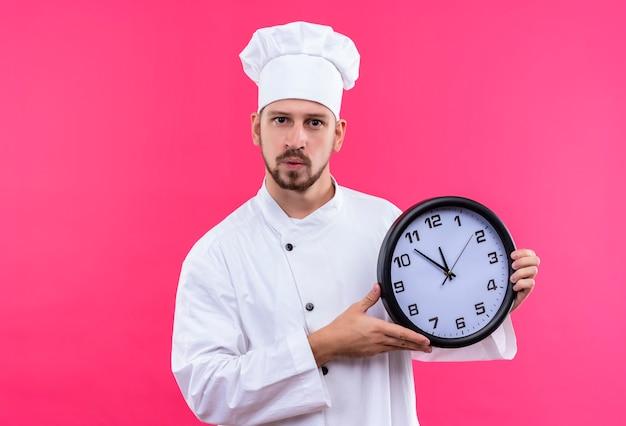 Professionele mannelijke chef-kok in wit uniform en kokhoed die een klok houdt die camera met zekere uitdrukking bekijkt die zich over roze achtergrond bevindt